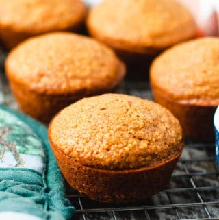 Close up view of vegan cornbread muffin sitting next to a green hotpad