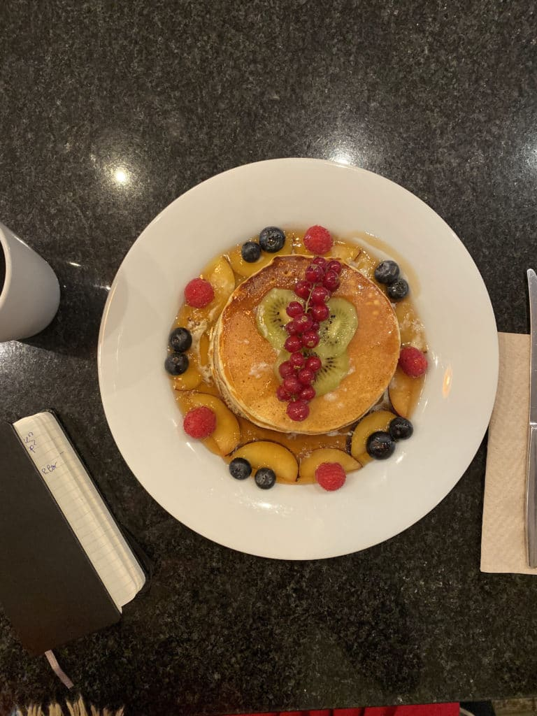 Pancakes covered in fruit on a large white plate