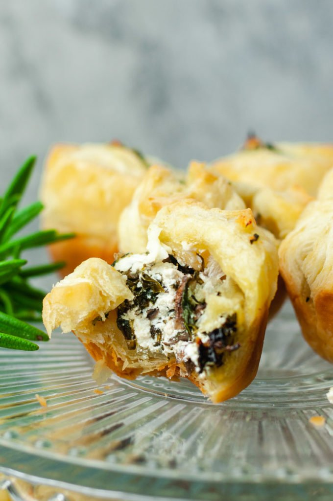 Close up of puff pastry with a bite taken out to show goat cheese filling