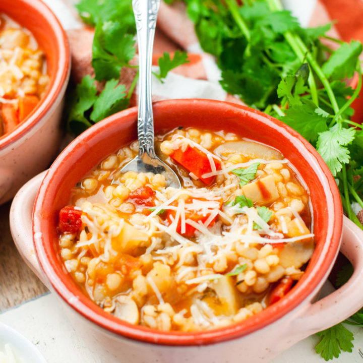 Pink bowl with barley soup topped with Parmesan