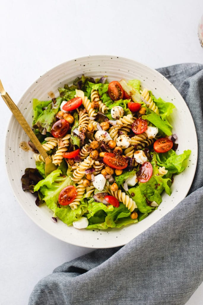 Vegetarian pasta salad in a large white speckled bowl on a gray cloth.
