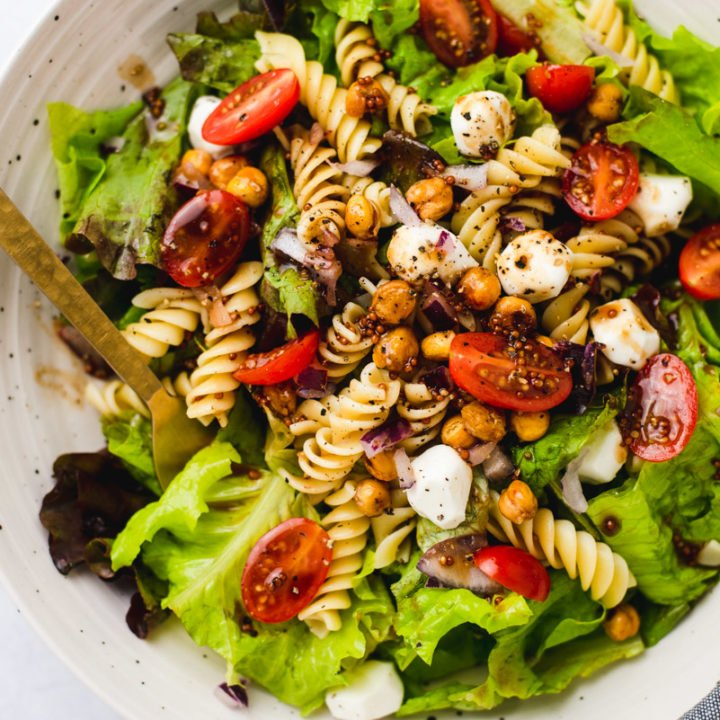 Close up view of rotini pasta, chickpeas, tomatoes on a bed of green lettuce in a white ceramic bowl.