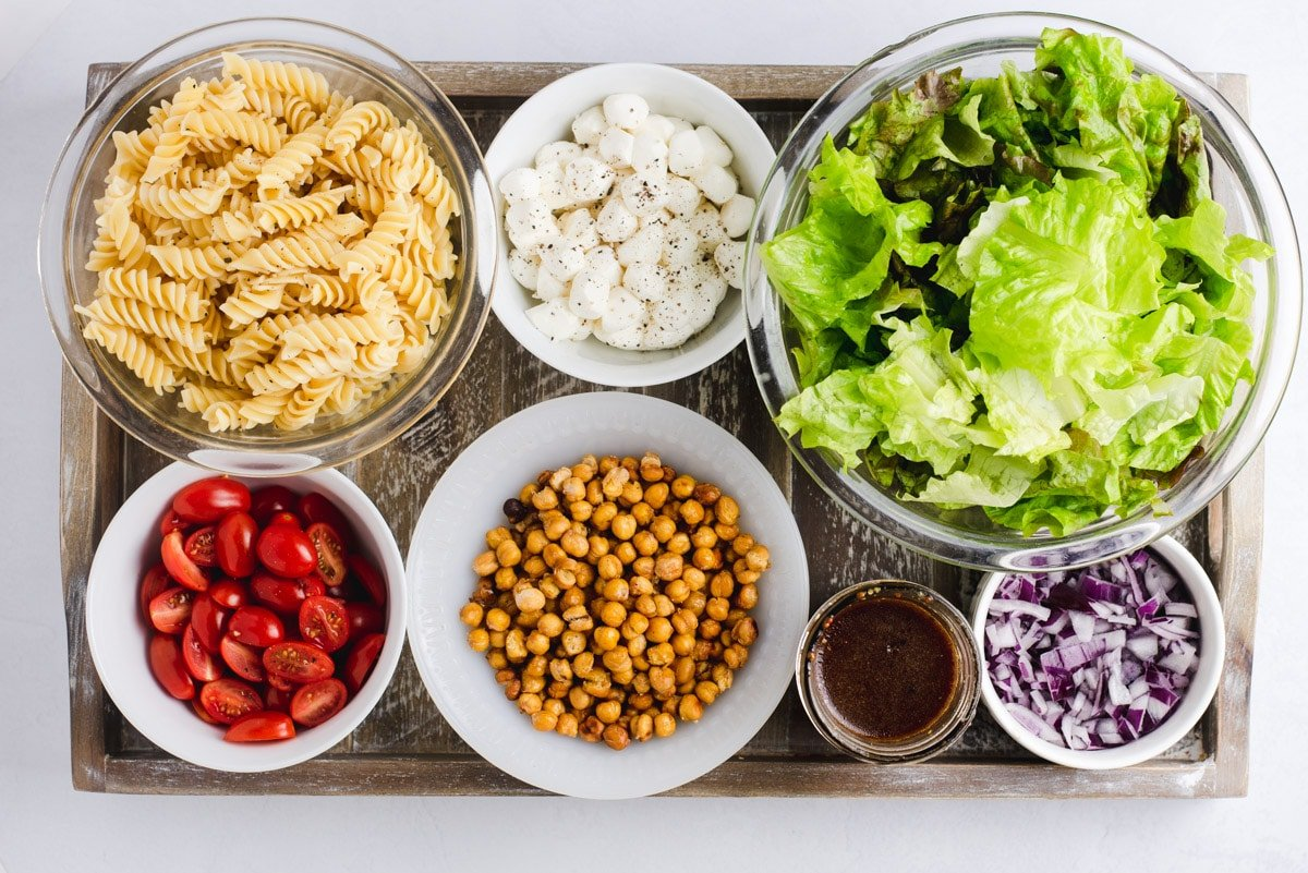 Ingredients used to make vegetarian pastas salads in separate bowls on a wooden board