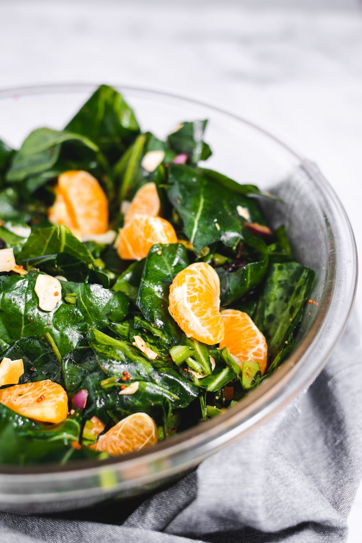 Close up of tangerine slices in a collard green salad