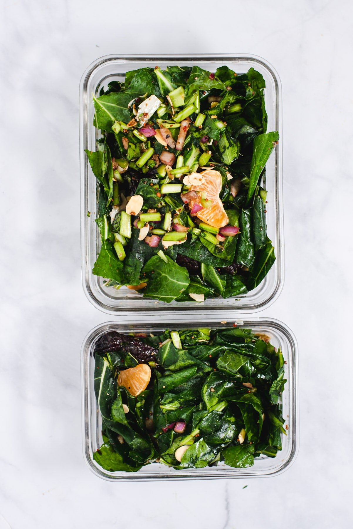 Two servings of salad portioned into glass containesr
