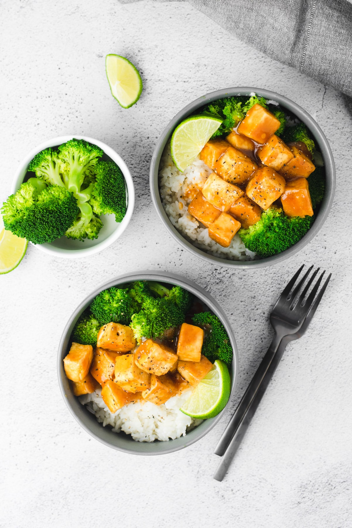 Two gray bowls filled with two servings of General Tso's tofu on a gray background