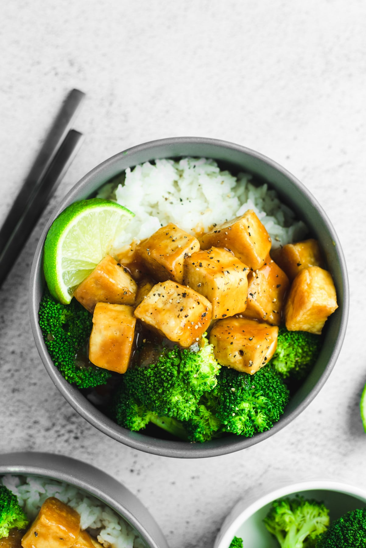 Gray bowl filled with white rice, orange colored tofu, and broccoli