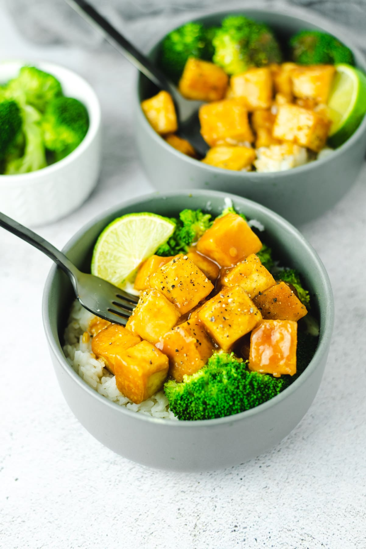 Two gray bowls filled with baked General Tso tofu