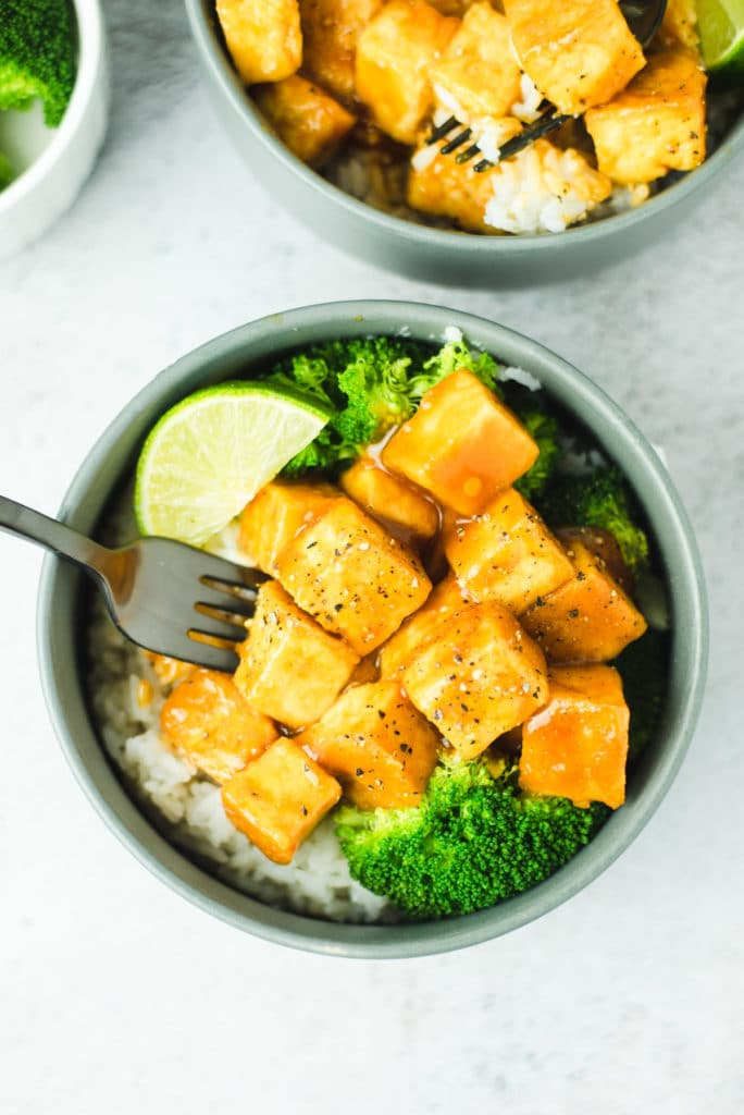 One serving of tofu in a gray bowl with white rice, steamed broccoli and a slice of lime