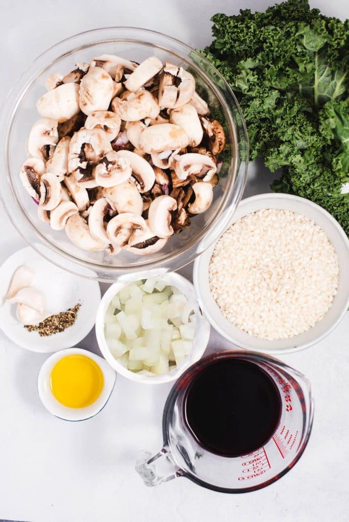 Onions, mushrooms, seasonings, wine and rice in separate bowls