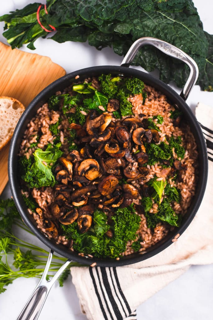 Sliced roasted mushrooms on top of a large skillet filled with risotto