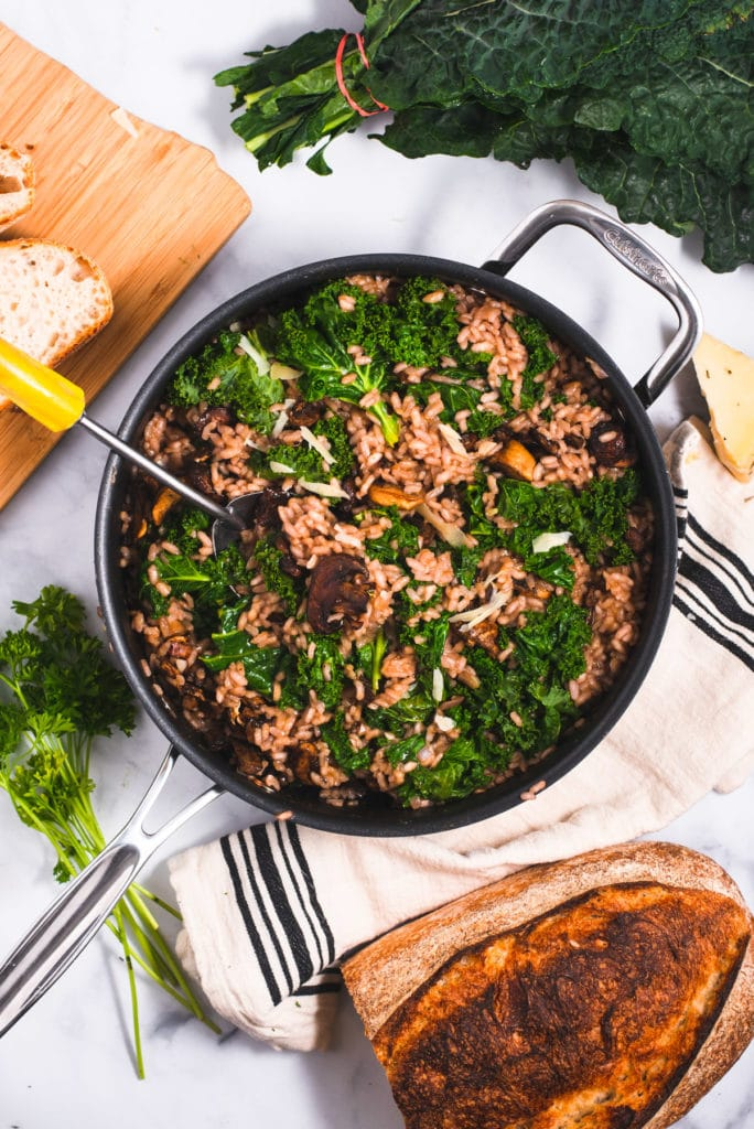Large skillet with mushroom risotto surrounded by a loaf of bread, parsley and Parmesan
