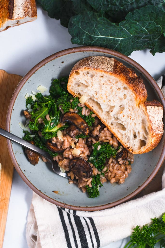 Blue bowl filled with risotto and a large slice of rustic bread