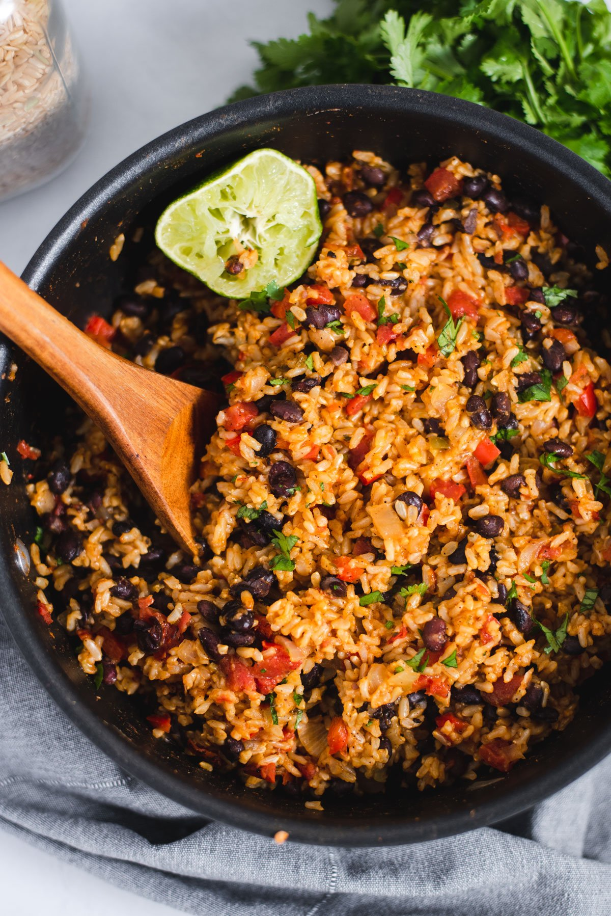 Large black pot filled with rice and beans and a wooden spoon