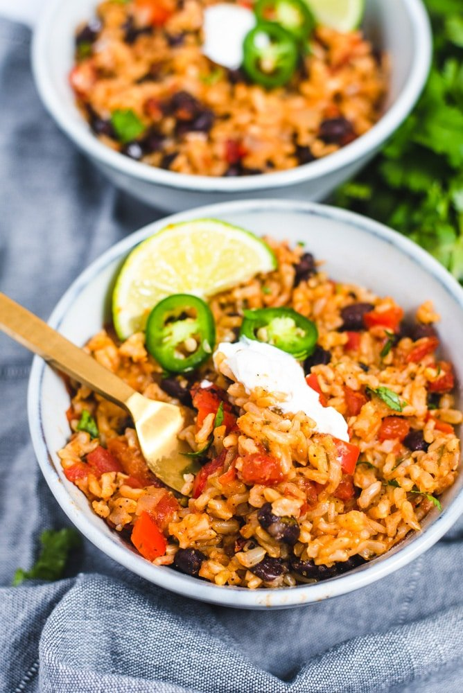 Light blue bowl filled with rice and beans topped with sour cream, fresh jalapenos and lime