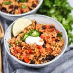 Bowl of rice and beans with a lime wedge and sour cream on top