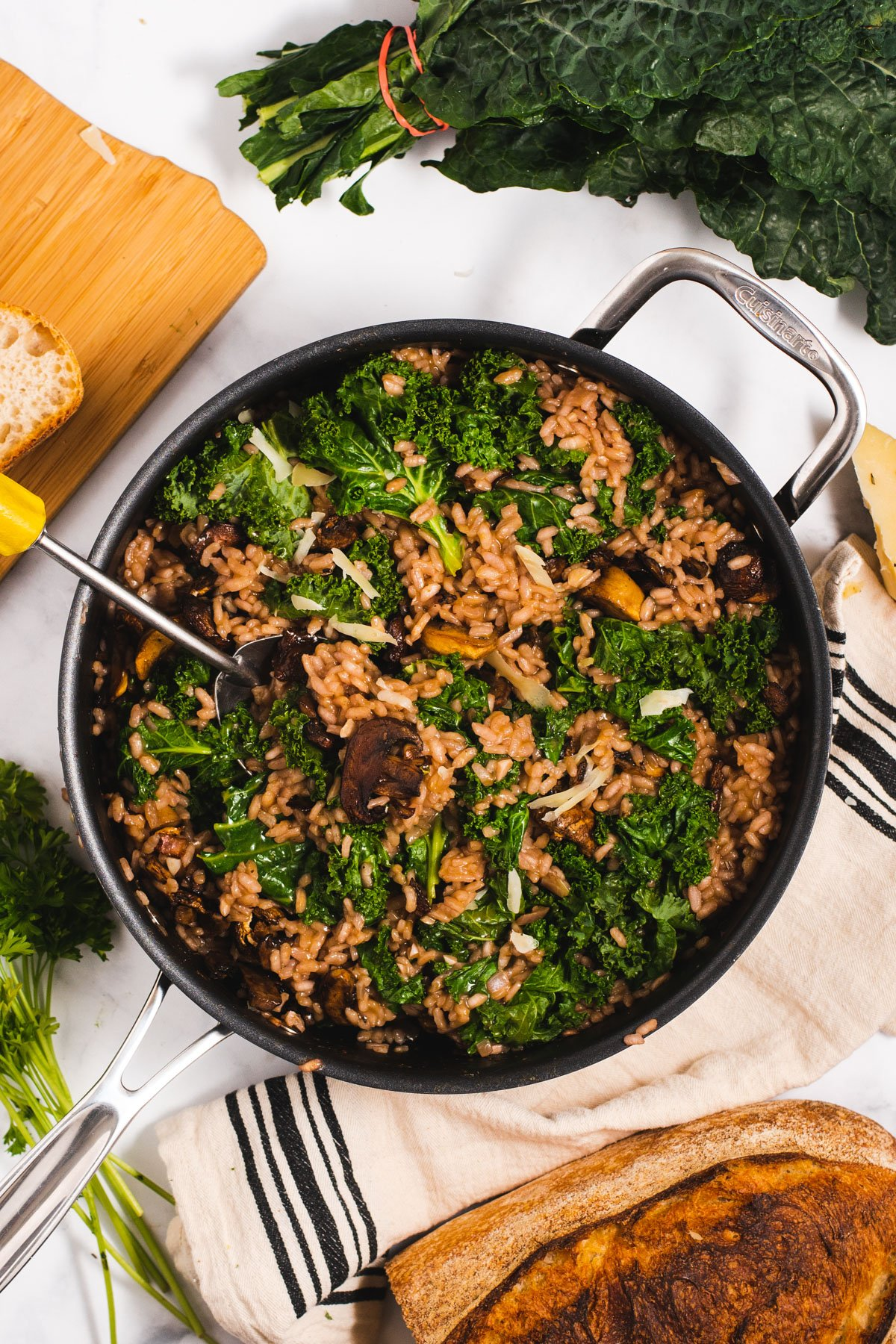 Large pan filled with risotto next to a loaf of bread, kale and a cutting board