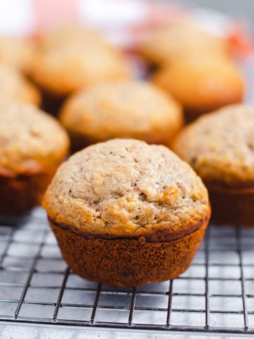 Close up side view of domed vegan banana muffin on wire cooling rack