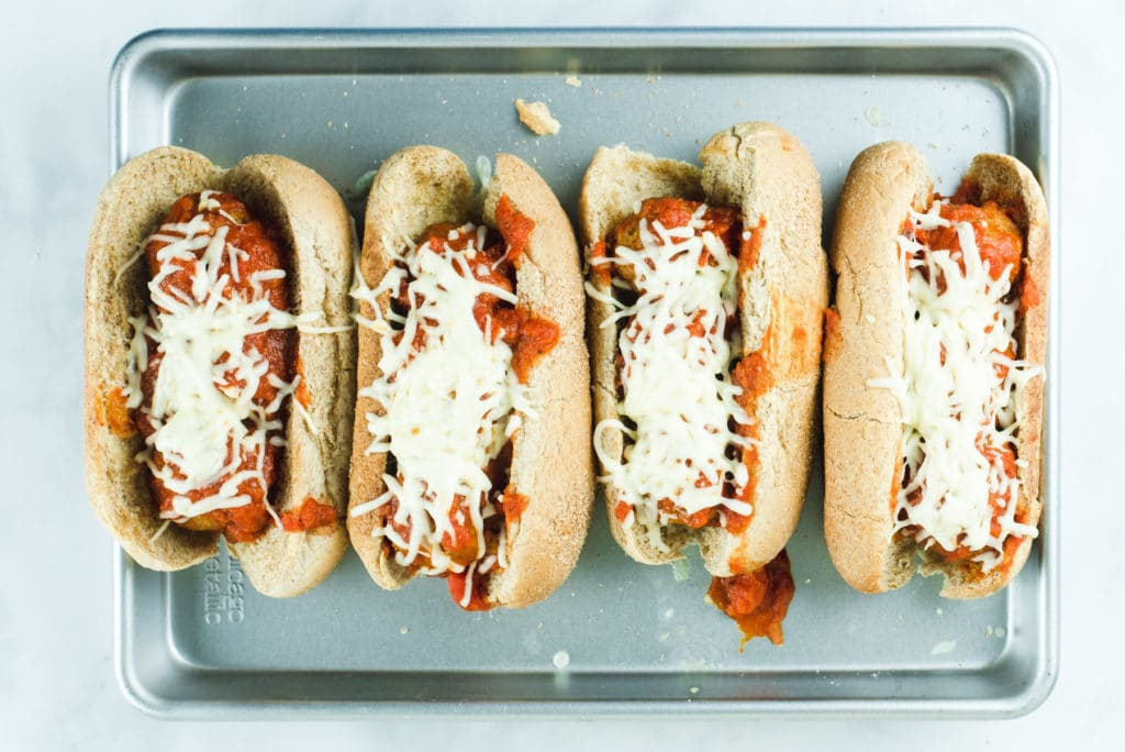Four vegetarian meatball subs showing melted cheese after being removed from the oven