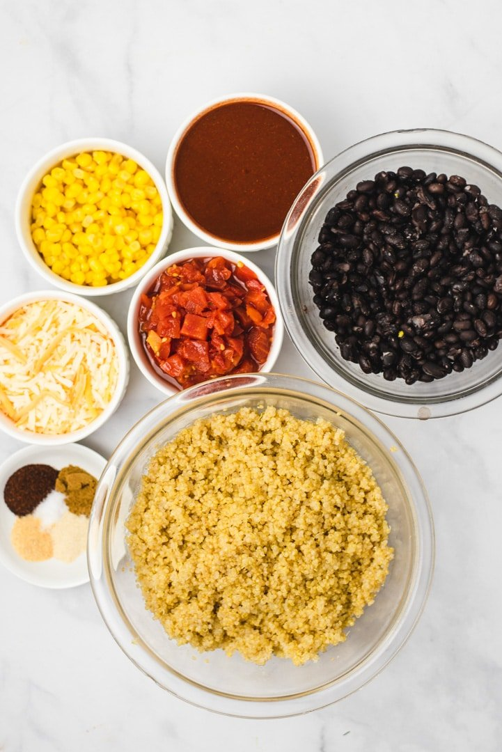 Ingredients used to make quinoa casserole in separate bowls on a marble countertop