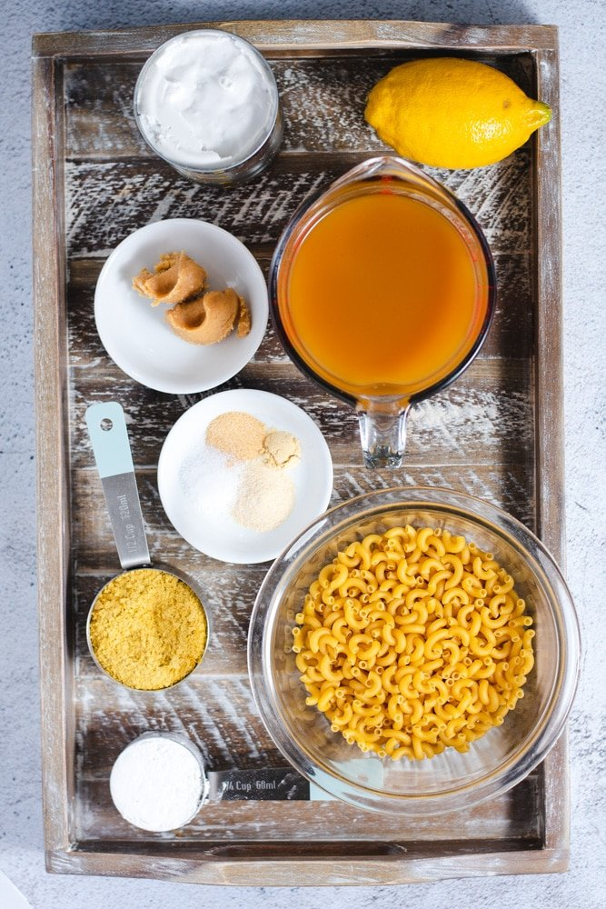 Ingredients used to make vegan mac and cheese on a wooden tray