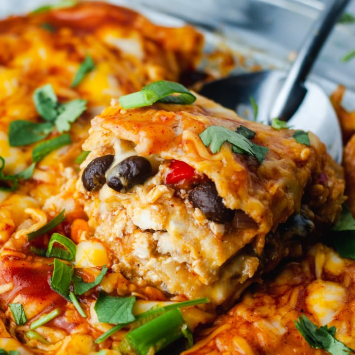 Slice of enchilada casserole with black beans being lifted out of a glass casserole dish.