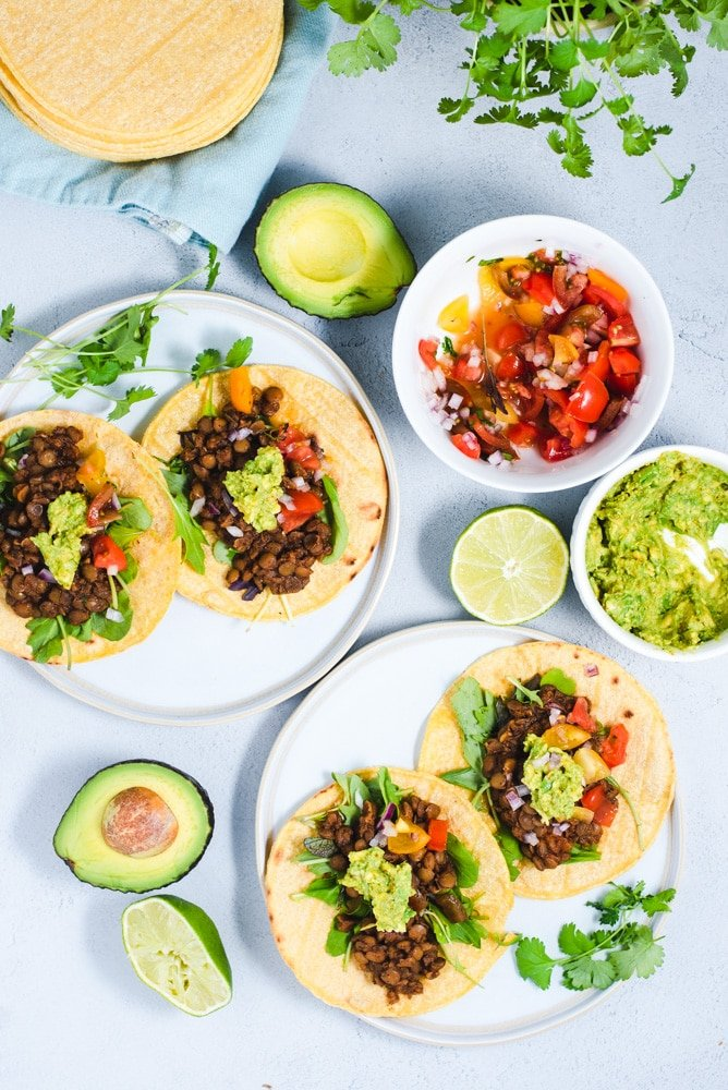 Two white plates with lentil tacos surrounded by bowl of salsa, guacamole and limes