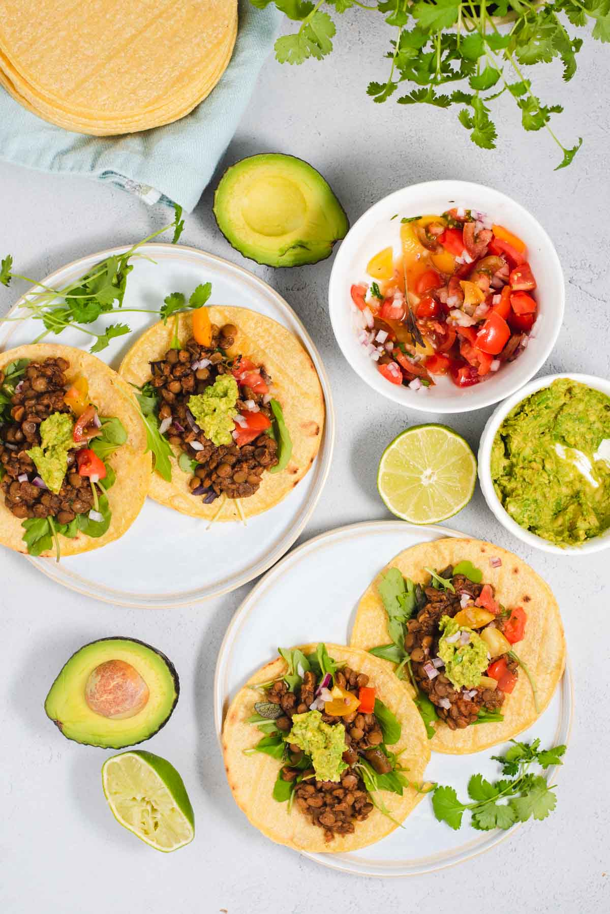Overhead view of four lentil tacos on white plates surrounded by salsa, guacamole and avocado