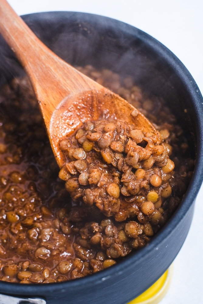 Close up of cooked lentils on a wooden mixing spoon