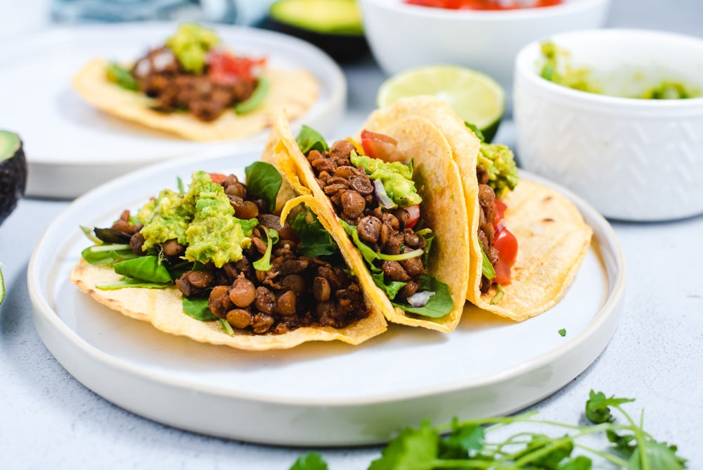 Three lentil tacos on a white plate