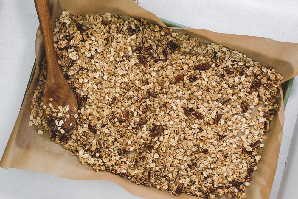 Maple pecan granola on a parchment paper lined baking sheet with a wooden spoon
