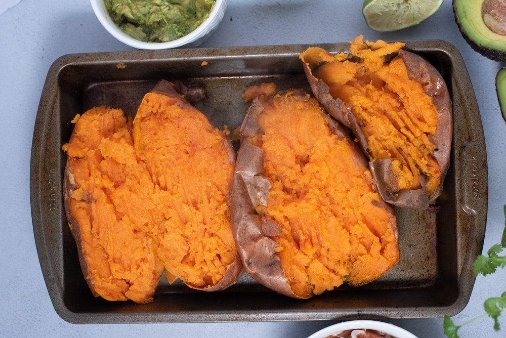 Three baked sweet potatoes sliced in half to show orange flesh