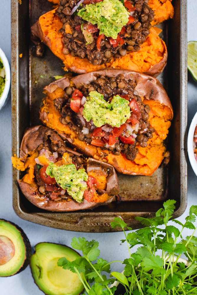 Two sweet potatoes topped with lentils, salsa and guacamole