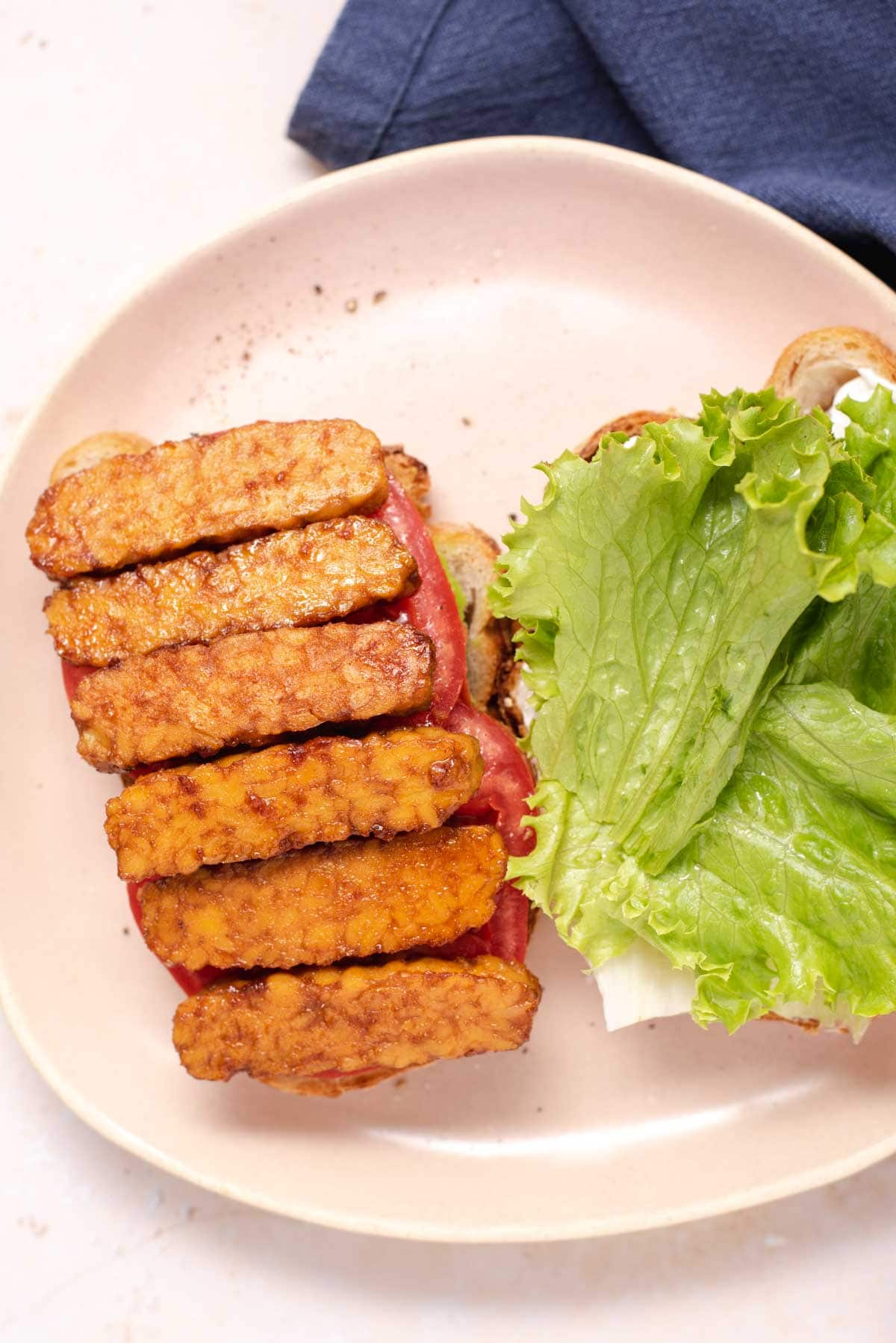 Six slices of tempeh on a sandwich half and romaine on a sandwich half