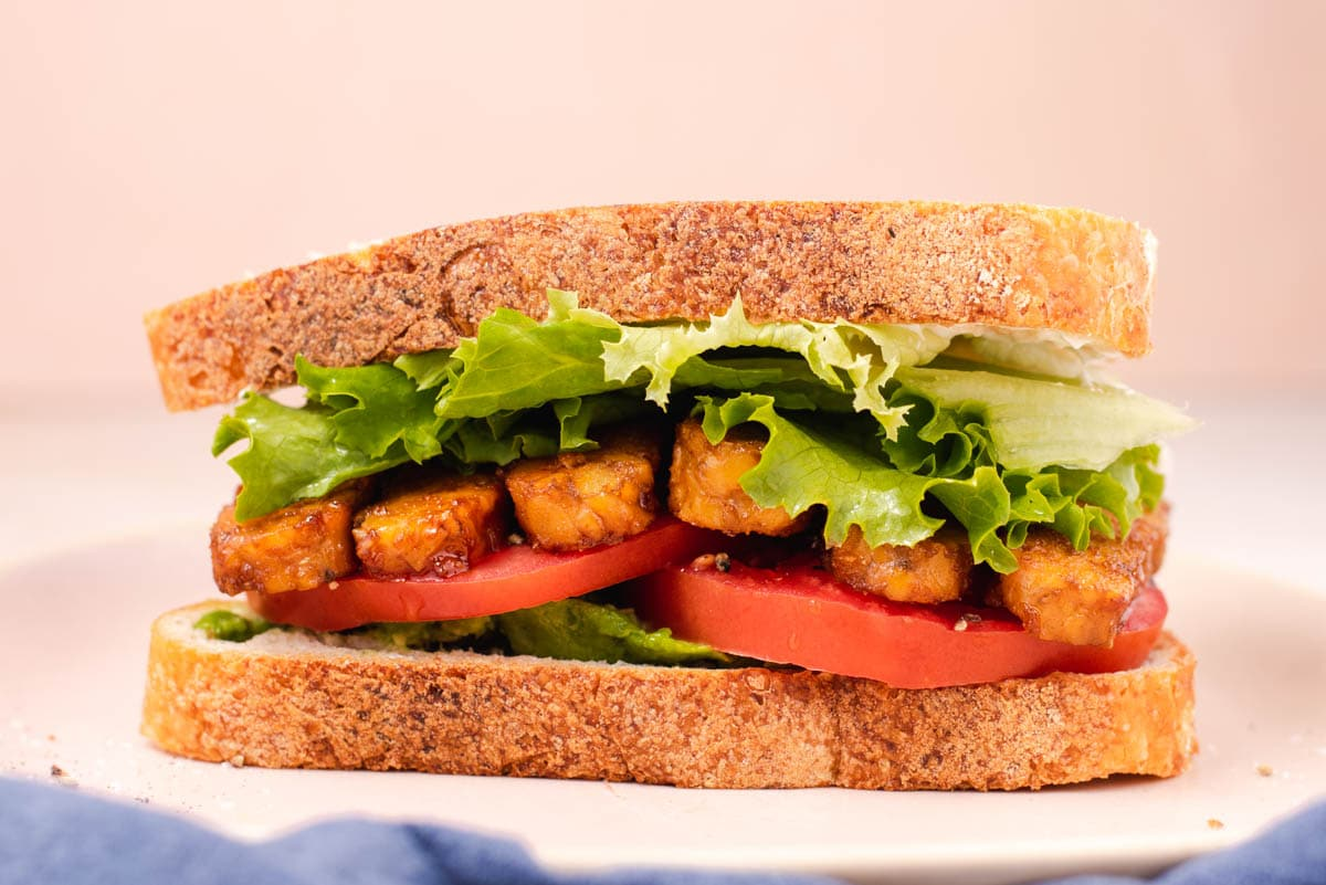 Tempeh lettuce tomato sandwich sitting on a pink plate