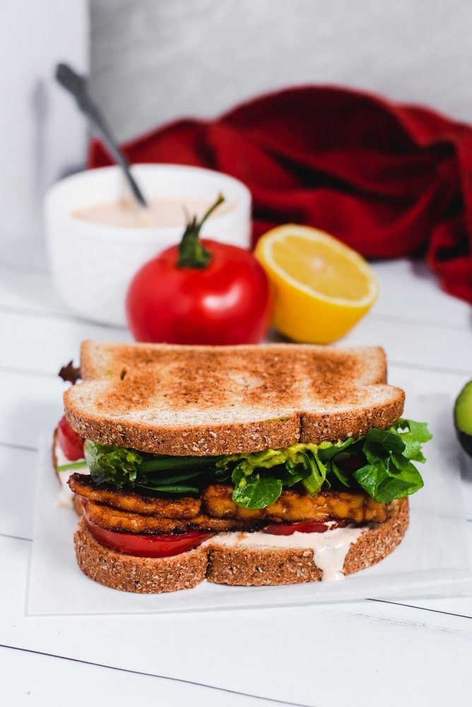 BLT in foreground with tomato, lemon and white bowl of aioli in the background