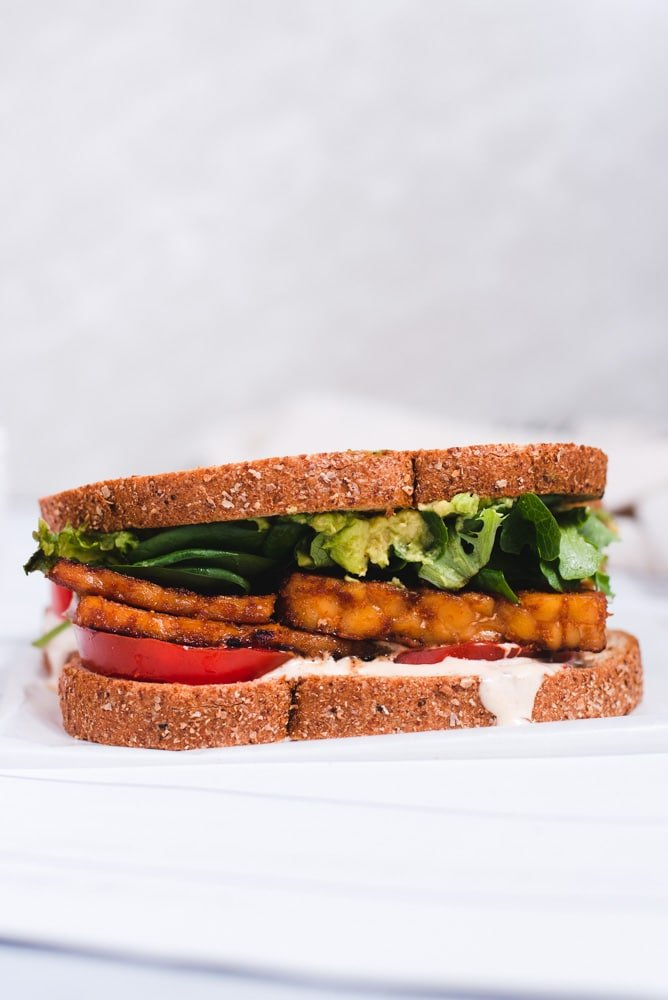 Tempeh BLT on a piece of wax paper in front of a gray background