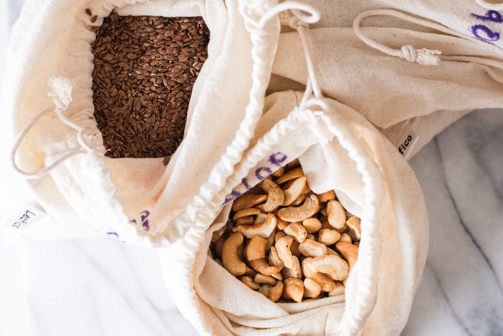Two cloth bags filled with cashews and flaxseeds