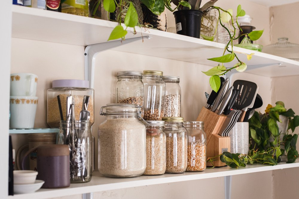 Grains and beans in a variety of glass jars on a white kitchen shelf