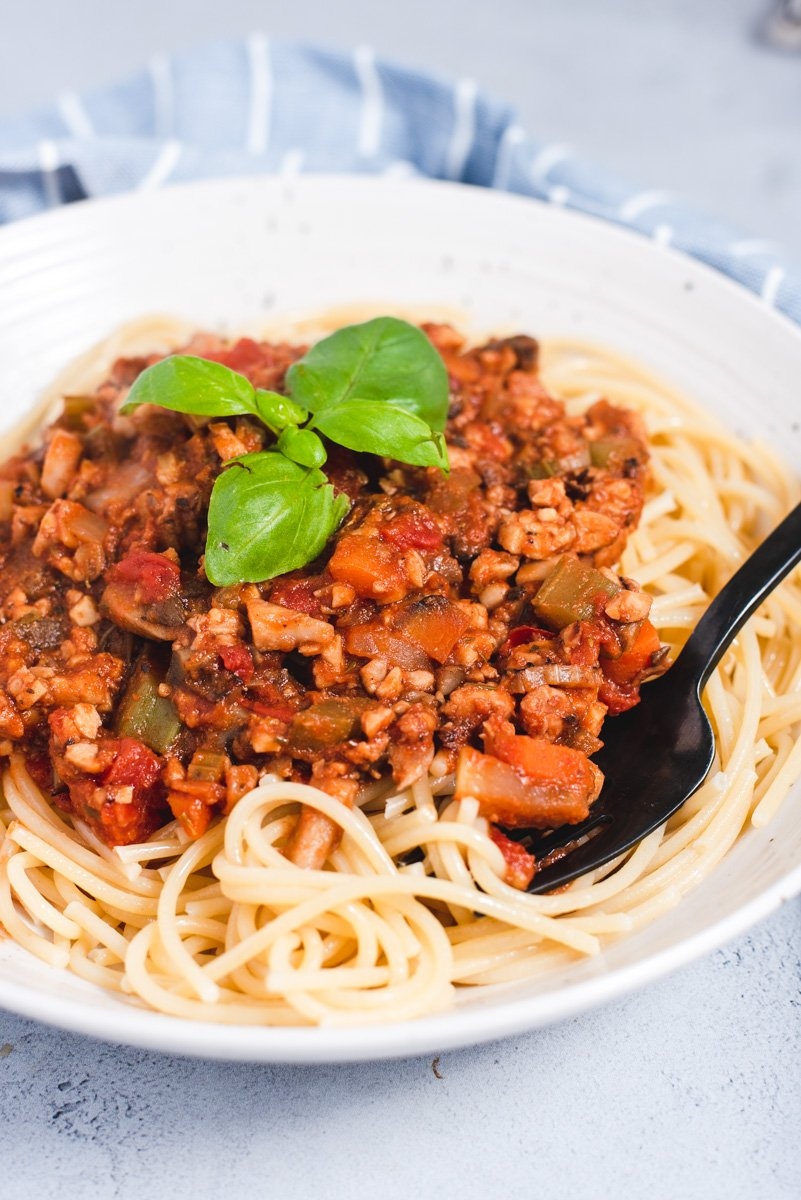 Close up of black fork in bowl of spaghetti and bolognese sauce