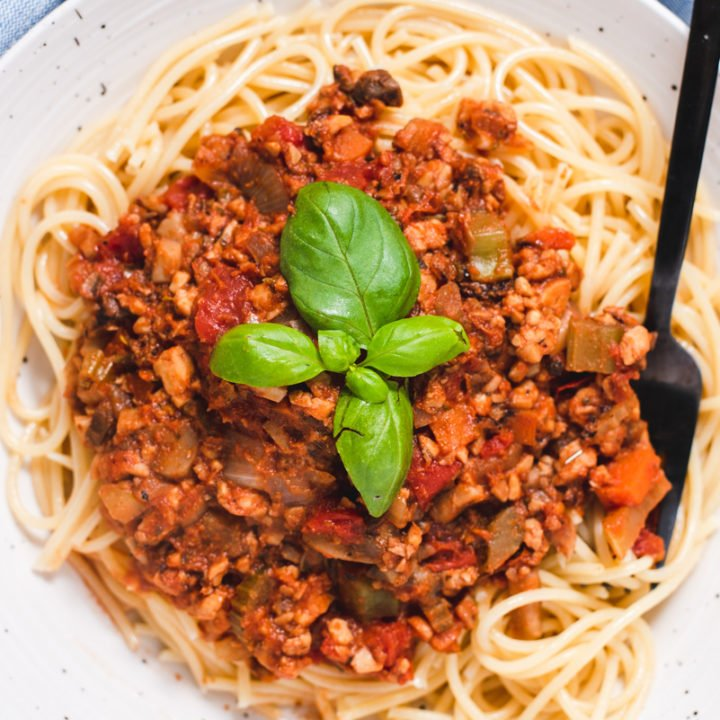 Large serving of spaghetti topped with bolognese sauce and fresh basil
