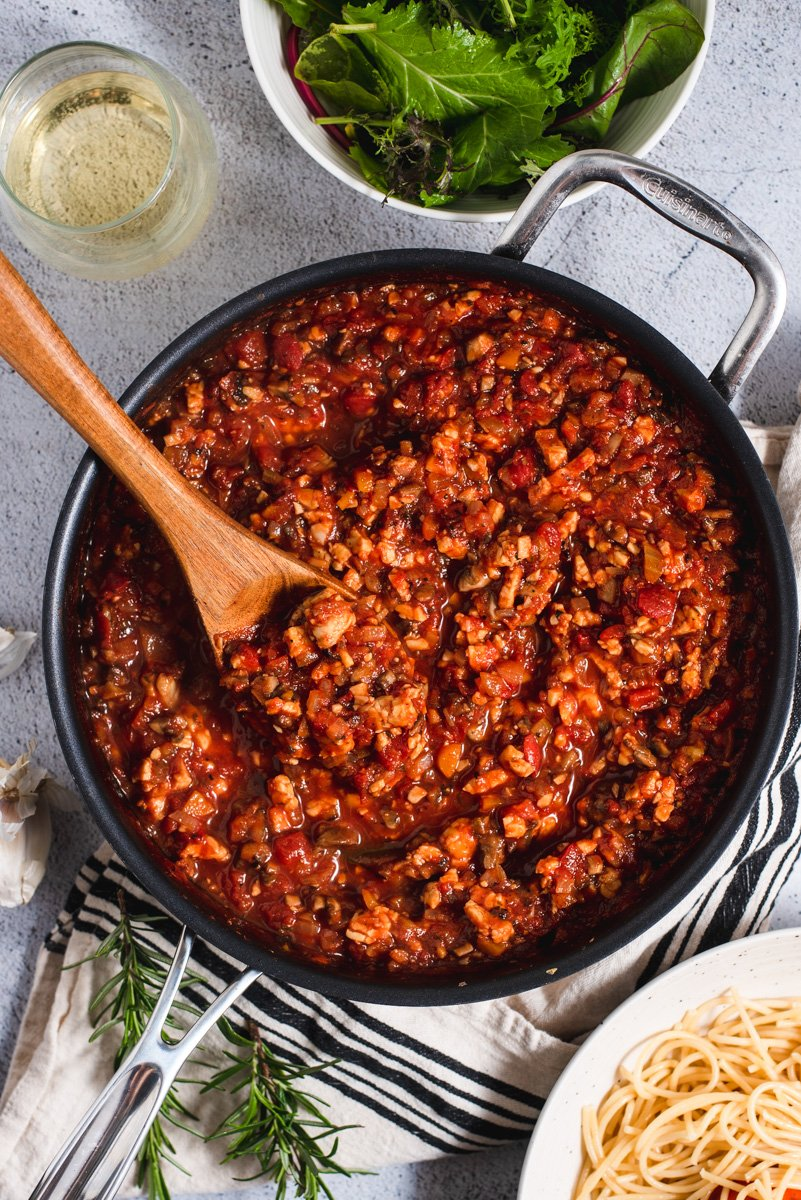 Tempeh bolognese sauce in a large black skillet with a wooden spoon