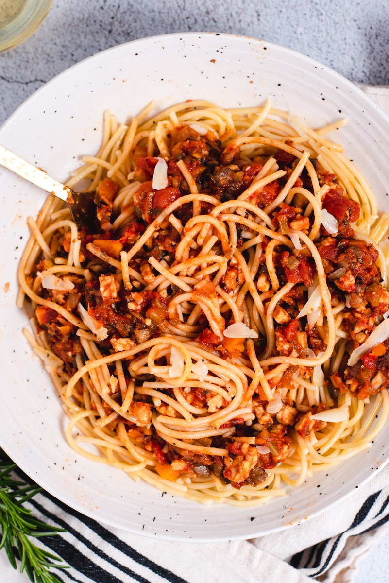 Spaghetti mixed with sauce in a white ceramic bowl