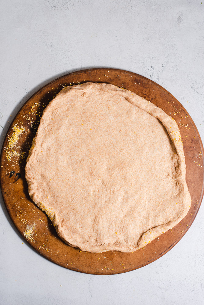 Raw pizza dough stretched out on a pizza stone