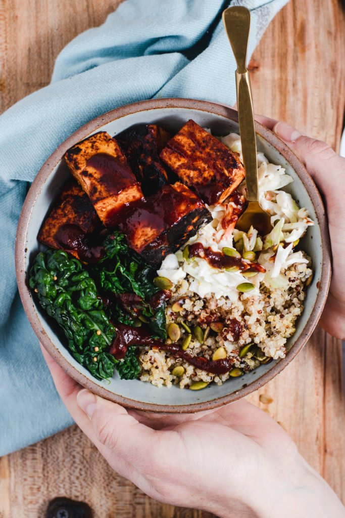 Hands wrapped around a blue bowl filled with tofu, kale, quinoa and coleslaw