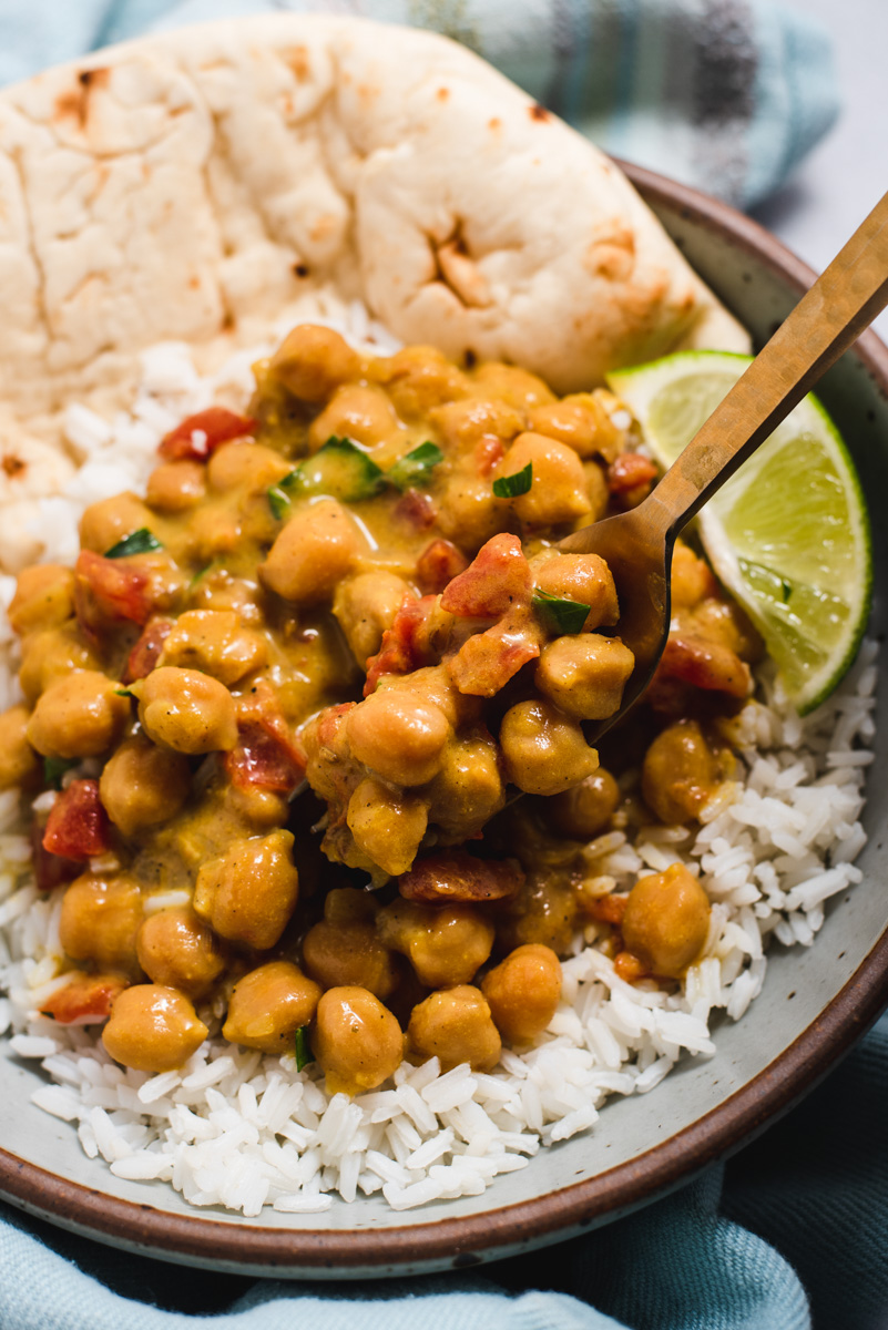 Chickpeas on white rice with naan and a lime wedge