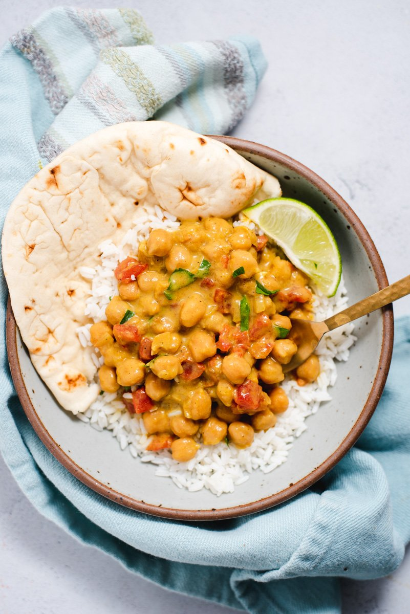 Chickpea curry on white rice with naan and a lime wedge