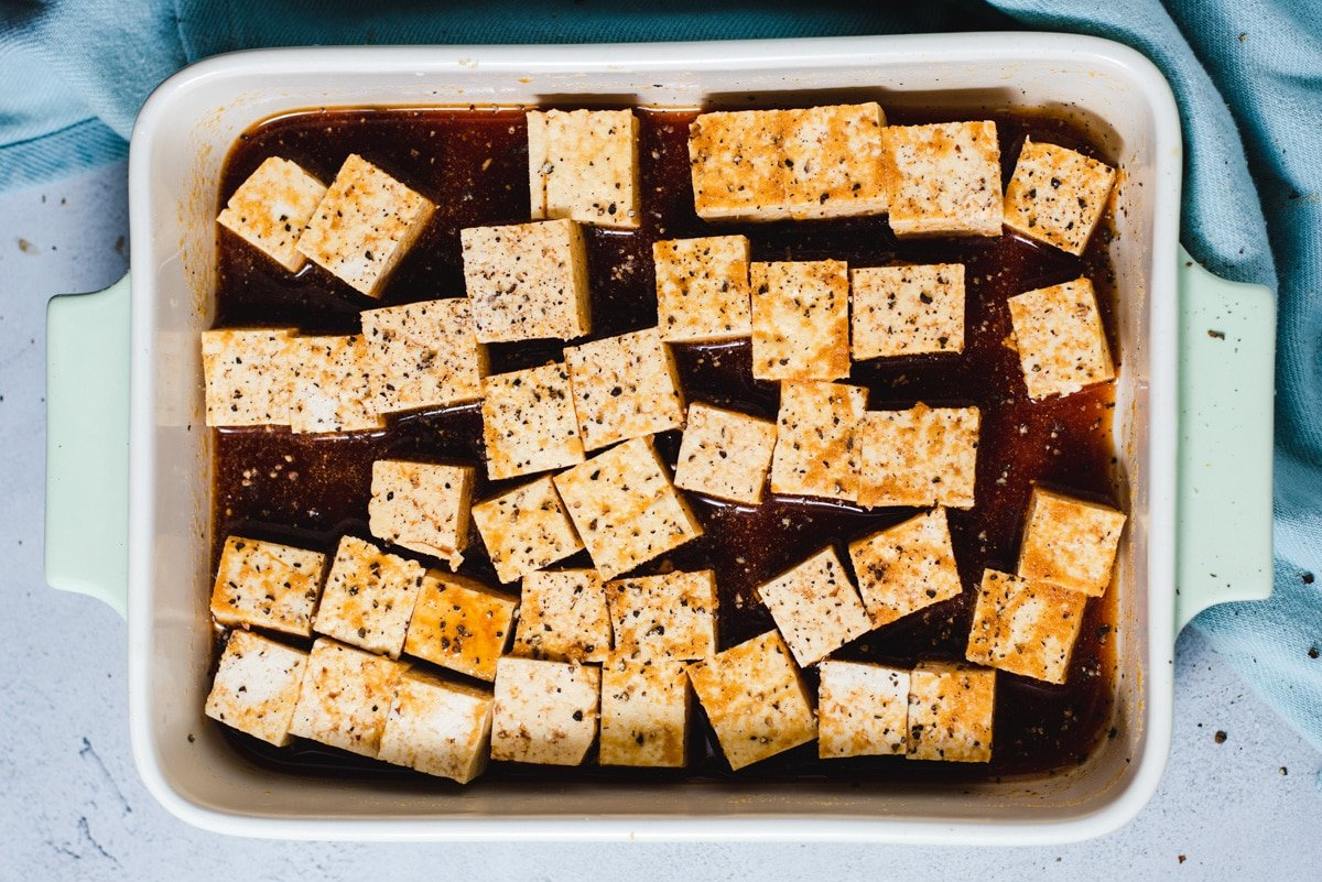Cubes of tofu in a white baking dish covered in marinade