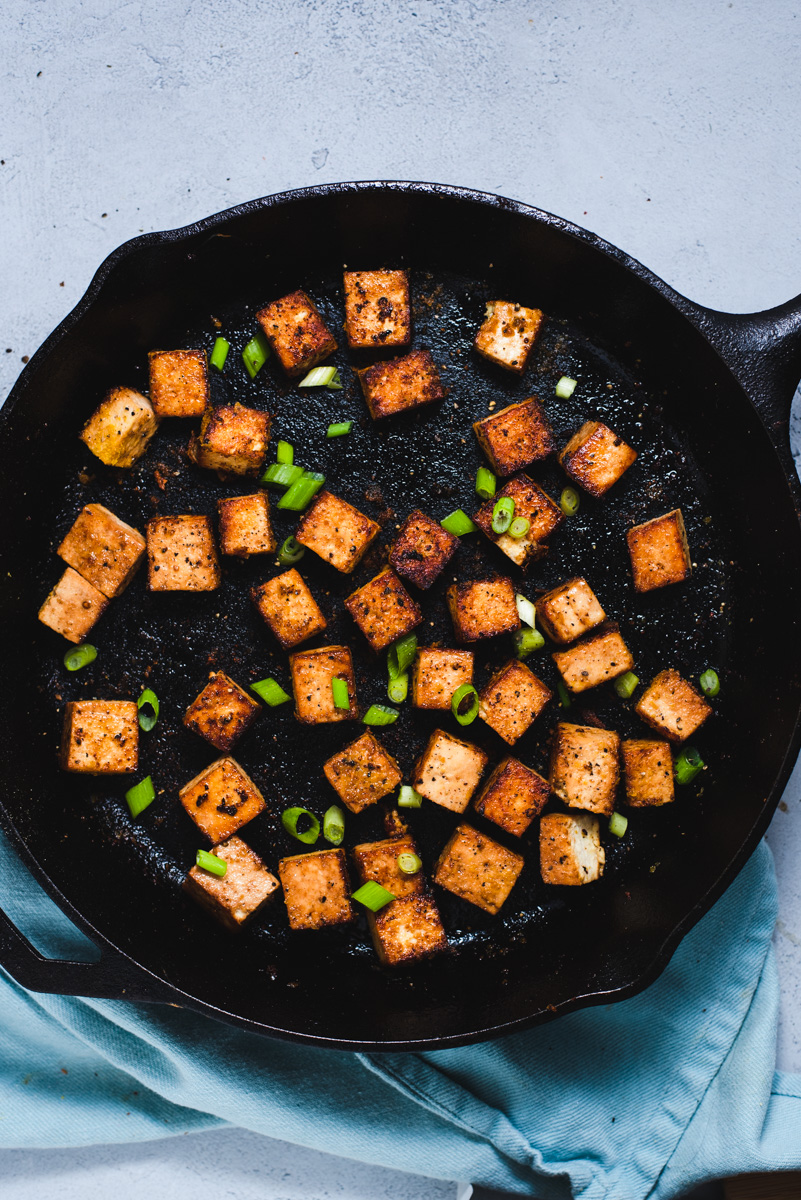Crispy cubes of tofu with sliced green onions in a black cast iron skillet