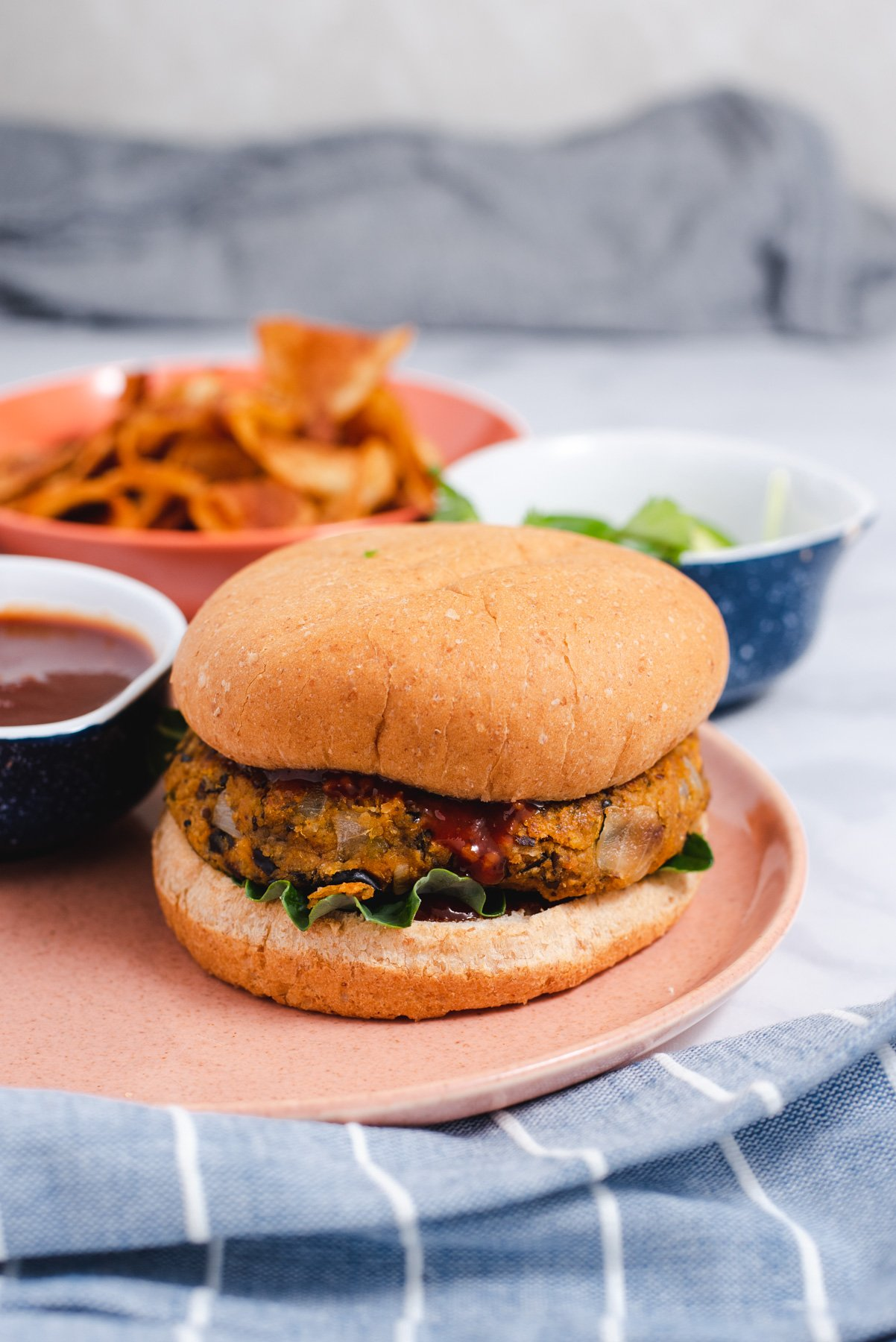 Sweet potato burger on a bun next to bowls filled with chips and barbecue sauce